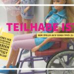 Foto von einigen Barbie-Puppen. Im Vordergrund sitzt eine schicke Barbie im Rollstuhl. Die Überschrift dazu lautet: Teilhabe ist: beim Spielen auch seinen Spaß zu haben.