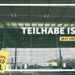 Foto vom BER (Vorderseite Eingangshalle des Flughafens). Die Überschrift lautet: Teilhabe ist: nicht umsonst.