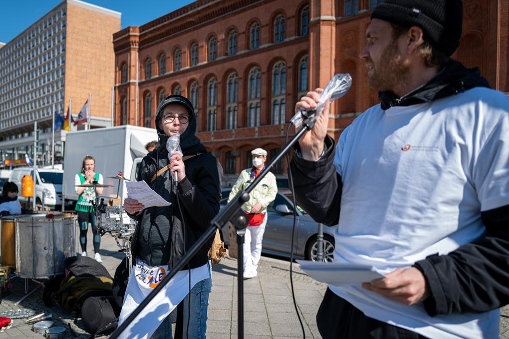 Frau und Mann mit Mikrophon in der Hand vorm Berliner Roten Rathaus