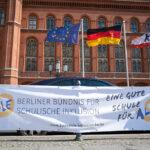 Banner mit Aufschrift Eine gute Schule für Alle, dahinter deutsche und europäische Flagge vor dem Roten Rathaus
