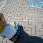 links im Bild Kind sitzt auf dem Gehweg schaut auf Kreidespruch Eine Schule für alle
