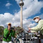 zwei Musiker mit Trommeln spielen, im Hintergrund der Fernsehturm