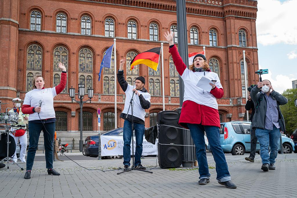 Zwei Frauen und ein Mann erheben die Hände und rufen etwas. Sie stehen vorm Roten Rathaus