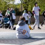 Kind sitzt auf der Erde, trägt weißes TShirt mit Aufdruck im Hintergrund Kinder und Erwachsene
